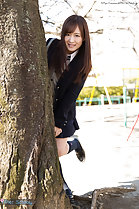 Student standing behind tree wearing uniform