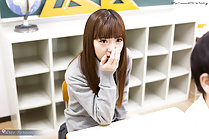 Nishino Ena seated with hand raised to her mouth