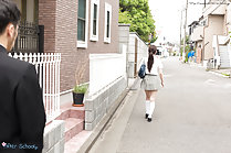 Student walking along street in uniform long hair in ponytail