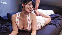 Lying on her front on bed wearing striped top and shorts