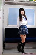 Student in uniform wearing plaid skirt long hair hands clasped behind her back