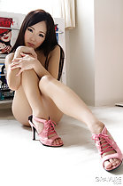 Seated naked hands on knee wearing pink heels
