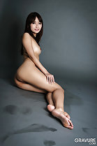 Sitting naked on floor looking past her shoulder small tit hand resting on thigh bare feet